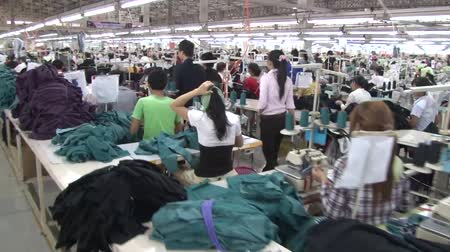 aisles : Wide shot following a group of unidentified monitors past aisles of seated workers in a garment factory