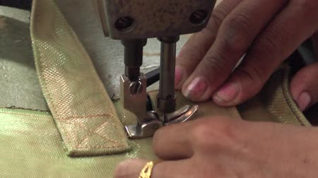 szycie : Female hands and head of sewing machine with needle as she stitches a heavy fabric handbag