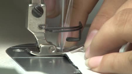 kumaş : Close up side view of industrial sewing machine needle with light colored fabric passing through Stok Video