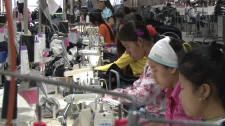southeast : Row of unidentified female garment factory workers working at their machines