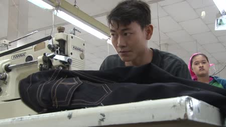 üretim : Garment factory worker sewing jeans at his sewing machine; other unidentified worker visible in background