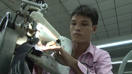 młyn : Male garment factory worker places dark heavy fabric strips into heavy industrial sewing machine