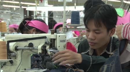 szycie : Male garment factory worker sews and then trims a garment while sitting at his machine