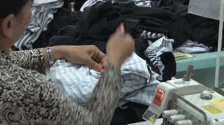 clothing : Female garment factory worker organizing a pile of completed garments at her sewing machine, then placing a barcode tag on them