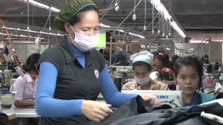 szycie : Middle aged female garment worker sorts and tosses completed jeans at her sorting table in the garment factory Wideo