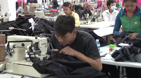 szycie : Male garment worker sewing jeans at his machine with great speed