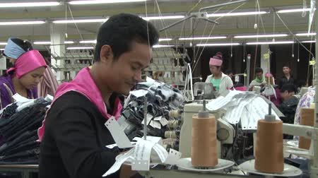 southeast : Male garment worker sews at his machine with large spools of thread in foreground. Other unidentified workers visible in background.