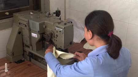 têxtil : Female garment industry worker operates her sewing machine with some equipment and spool of thread in foreground.