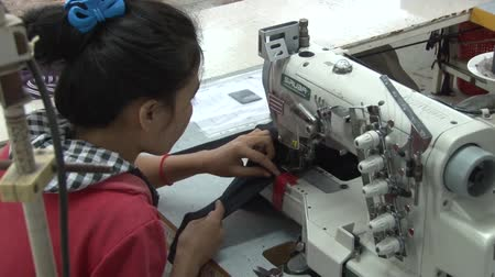 młyn : Garment worker sews fabric sections in sewing machine at garment factory