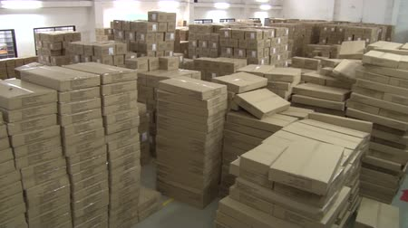 szycie : High angle pan across stacks of boxes in garment factory warehouse with unidentified workers in background