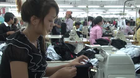 kumaş : Garment worker sews striped fabric sections in heavy sewing machine, with other unidentified garment workers and factory ambience in background