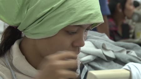 southeast : Female garment worker with green scarf as she intently focusses on operating her sewing machine