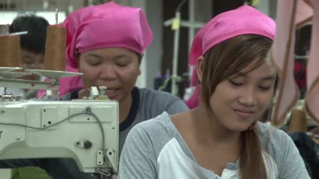 młyn : Female garment worker in foreground with middle aged unidentified female garment worker at the machine behind her.