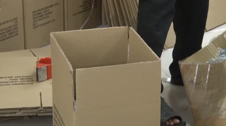 southeast : Male garment worker tapes and seals a box of completed garments in the warehouse area of a garment factory, with stack of many boxes nearby Stock Footage