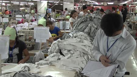 szycie : Factory supervisor holds and reads clipboard, while unidentified garment workers work at their machines and pass by in the background
