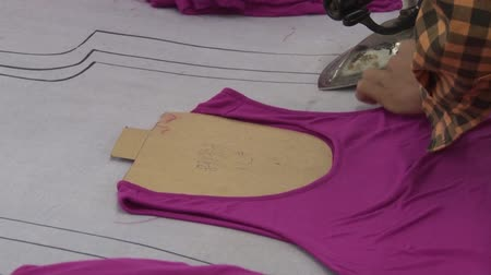 clothing : Close up female garment worker hands and arms preparing completed purple tank tops for ironing; she then steams and irons garments