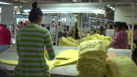 indústria : Reverse of female garment worker sorting yellow completed garments at her station; other unidentified garment workers visible in background