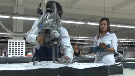 üzleti öltöny : Garment factory worker cuts fabric pieces with an electric bandsaw, while unidentified supervisor monitors progress nearby