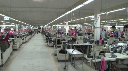 clothing : Pan from right to left showing numerous unidentified garment workers engaged in different activities on the factory floor Stock Footage
