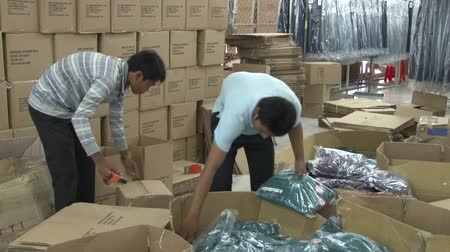 szycie : Unidentified male workers organize completed garments into boxes, with rows of packed boxes behind them Wideo