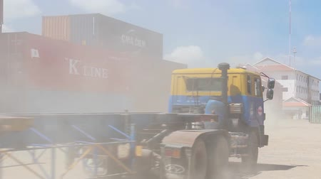konténer : Two flatbed trucks carrying shipping containers move through a dusty Asian port and drive away; shot reframes to telephoto cu of second truck