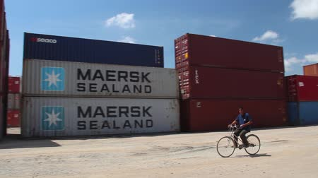 veículo aquático : Port worker bicycles through shipping container storage area in Asian port, pan to follow
