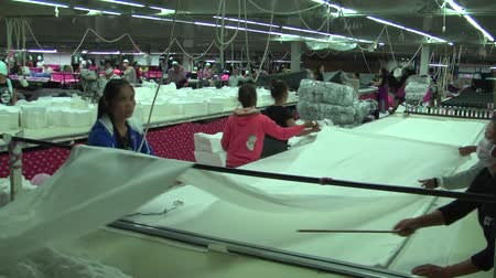 młyn : Wide shot garment workers unspool a large white roll of fabric in preparation of cutting and preparation