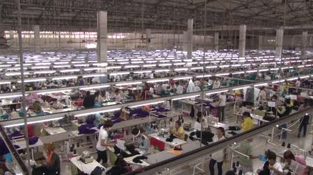 indústria : Superb high angle wide shot overview pan from left to right of large garment factory floor, with hundreds of unidentified garment workers below