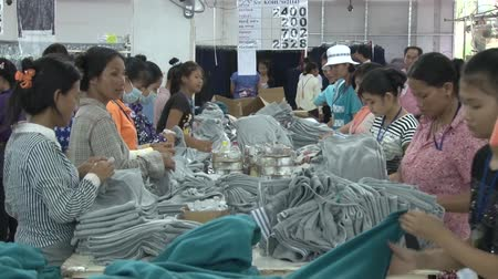 southeast : Numerous unidentified garment workers fold and prep completed grey and blue sweatshirts Stock Footage