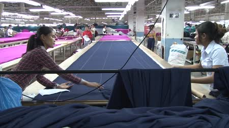 szycie : Garment workers pull a length of blue fabric from a spool and extend it down a long table, in preparation for measuring and cutting