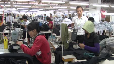 têxtil : Garment workers sewing at their stations with unidentified supervisor standing nearby monitoring their work