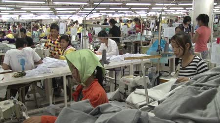 southeast : 2-shot of unidentified garment workers sewing and sorting grey sweatshirt sections in a garment factory