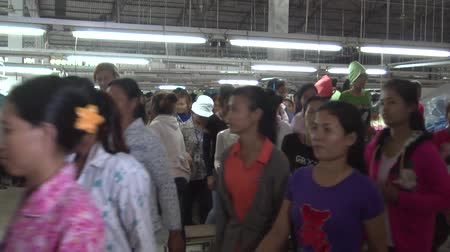 szycie : Numerous unidentified garment factory workers stepping up and through inspection as they pass the camera on their way to lunch break