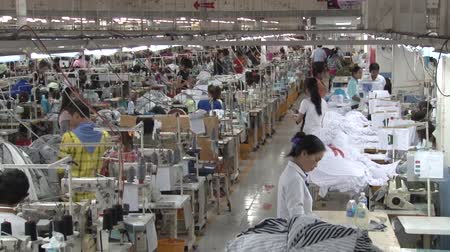 indústria : Zoom out and settle on wide shot of numerous unidentified garment factory workers in factory, with perspective down aisle as one workers walks away