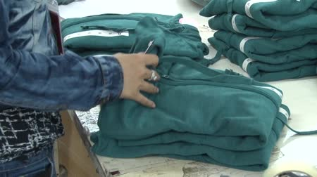 clothing : Medium close up garment worker hands and arms sorting, prepping, then bagging completed garments to prepare for shipping