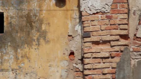 sıva : Medium shot pan across ruined french colonial wall in Asia with bricks and broken plaster visible Stok Video