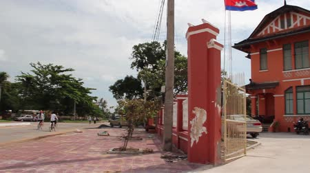 руины : Pan from unidentified cyclists to restored orange colored French colonial administration building in small town in Asia, with Cambodian flag flying nearby Стоковые видеозаписи