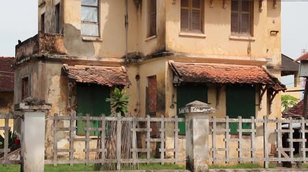 moderno : Very dilapidated old French colonial building in Asia, with broken stucco and missing rooftiles; settle on aged concrete fence