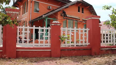 mohás : Orange colored French colonial administration building in Southeast Asia; orange and white fence in foreground