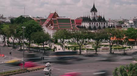 múlt : Time Lapse wide shot of daytime traffic passing in front of palace in Bangkok, Thailand; polarized clouds move past Stock mozgókép