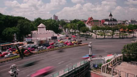 portugese : Time Lapse wide shot of daytime traffic passing through intersections in Bangkok, Thailand, with metal palace visible in distance and old Portugese fort