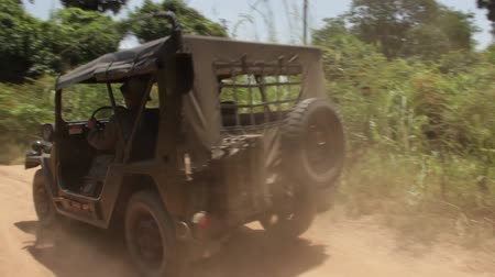 war : Vintage Vietnam war era olive drab Jeep passes on dusty country road in Southeast Asian countryside; contemporary footage which can be used for 1970 period productions and recreations Stock Footage