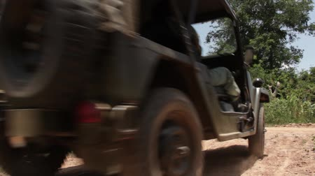 war : Low Angle road level Vintage Vietnam war era olive drab Jeep passes quickly on dusty country road in Southeast Asia, turns left;contemporary footage which can be used for 1970 period productions and recreations