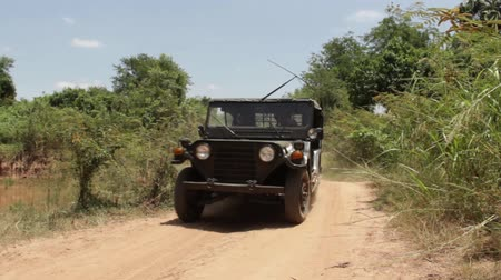 war : Telephoto Vintage Vietnam war era olive drab Jeep approaches on dusty country road in Southeast Asia; shot reframes to wide shot, then Jeep passes. Contemporary footage which can be used for 1970 period productions and recreations