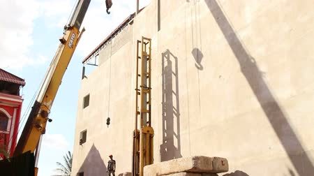 empilhamento : A large crane lowers a dangling hook, pulley, and tackle to the ground on this construction site in Asia; excellent shadow of the action is repeated on the opposite wall.