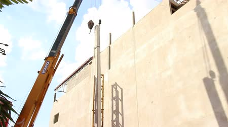 hidráulico : A long concrete pile whirls and rotates as it is moved, suspended by a crane and cable, into place at a nearby pile driver framework Stock Footage