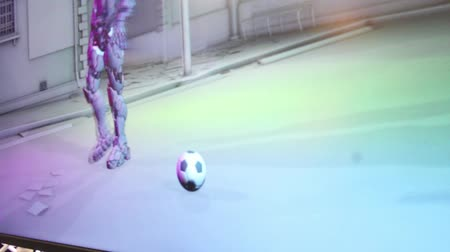 valóság : A technical staffer demonstrates the functionality of a motion capture system, using a specially rigged suit and football aka soccerball  One of a series of gaming industry and virtual reality technology clips  Stock mozgókép