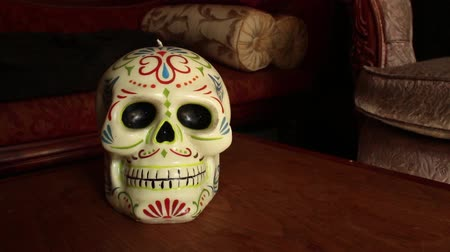mortal : DOLLY MOVE WITH SKULL: Skull is Cinco de Mayo style, made of Wax, on Wooden table with Vintage couch   CURRENT SHOT One of a Series - Dolly into skull and hold at medium close up; continue forward into skull.