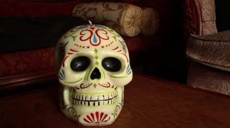 mortal : DOLLY MOVE WITH SKULL: Skull is Cinco de Mayo style, made of Wax, on Wooden table with Vintage couch - Dolly out from ECU skull, hold at medium close up; continue dolly out to wider shot Vídeos