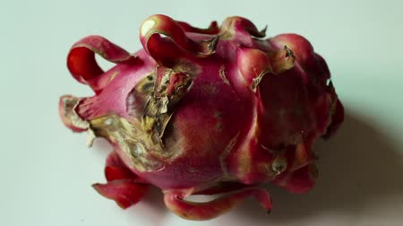 etli : Medium close up dolly right and return again over a very ripe red Asian dragon fruit